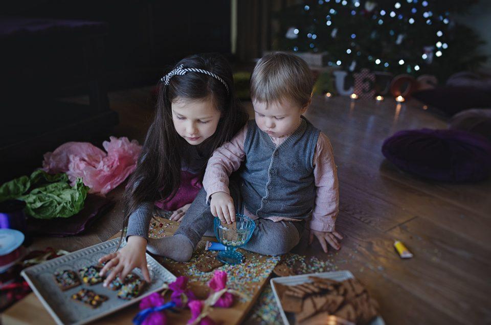 Vaikai valgo imbierinius sausainius Kalėdinėje šeimos fotosesijoje