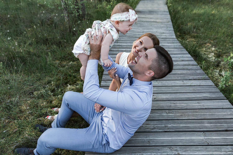 Kūdikis aukštai iškeltas krykštauja šeimos fotosesijoje gamtoje