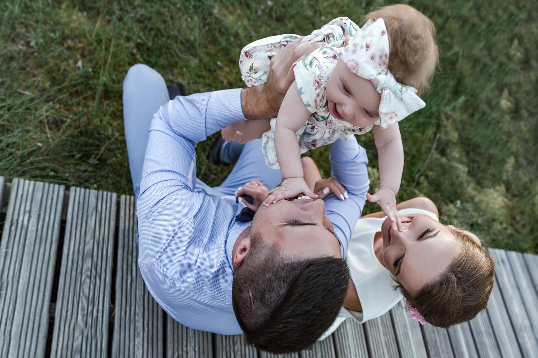 Kūdikis žaidžia su tėvais šeimos fotosesijoje gamtoje