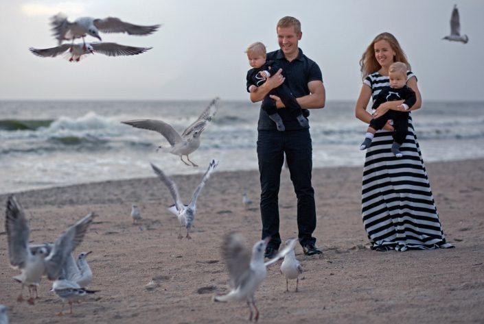 Šeimos fotosesija prie jūros skraidančių žuvėdrų apsuptyje