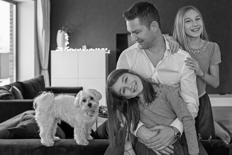 tėtis su dukromis fotografuojasi savo namuose. šalia stovi šuo
