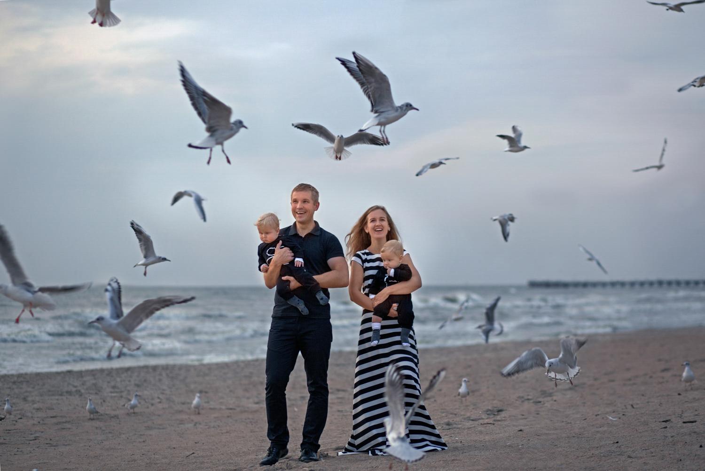 Šeimos fotosesija prie jūros tarp skraidančių žuvėdrų
