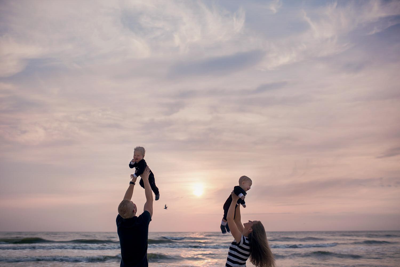 Berniukai šeimos fotosesijoje prie jūros krykštauja iškelti į orą