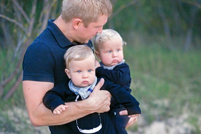 Tėtis laiko dvynukus prie jūros šeimos fotosesijoje
