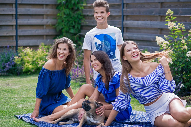 mama su vaikais juokiasi susėdę ant pleduko namų kieme per šeimos fotosesiją