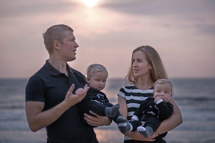 Šeima prie jūros palydi saulę