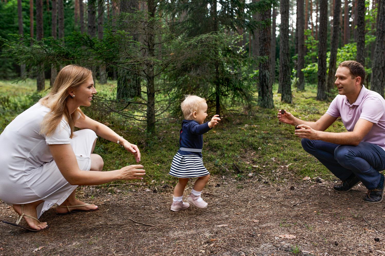 mergaitė eina pas tėtį per šeimos fotosesiją miške