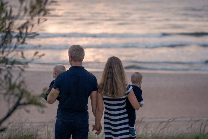 Šeima prie jūros grožisi saulėlydžiu per šeimos fotosesiją