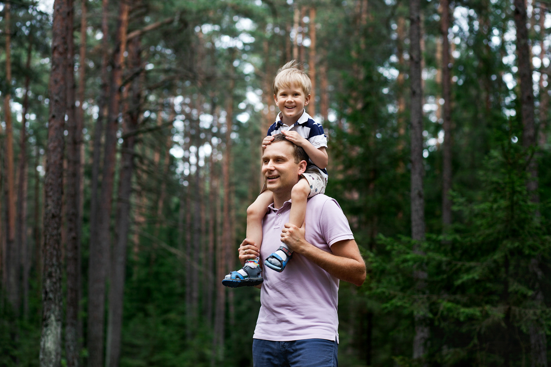 tėtis neša vaiką ant pečių šeimos fotosesijoje miške