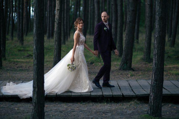 Jaunavedžiai eina kopų takeliu, per pūšų kamienus vestuvių fotografas fotografuoja juos