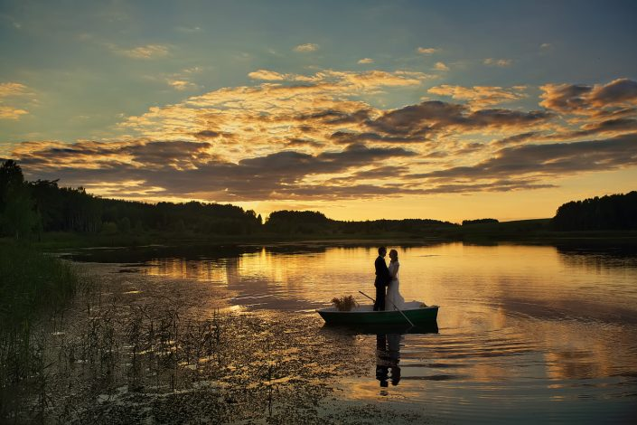 vestuvių fotografas fiksuoja jaunavedžių akimirkas saulėlydyje plaukiojant valtimi ežere