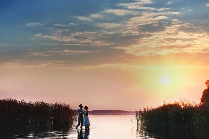 jaunavedžiai šoka ežere. Vestuvių fotografas fiksuoja akimirkas saulėlydyje