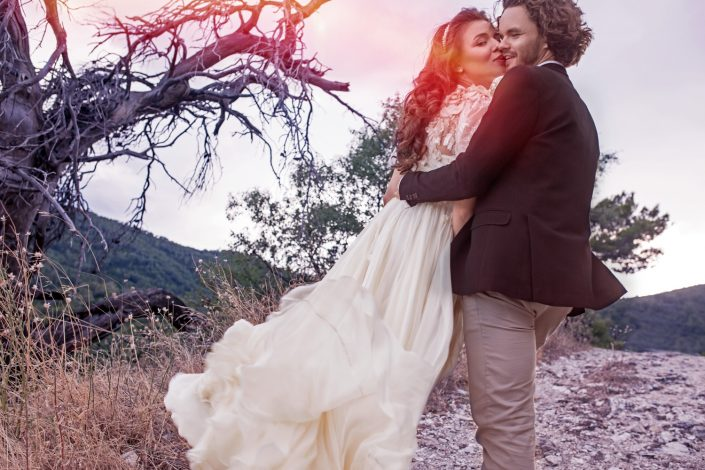 vestuvių fotografas fiksuoja akimirką, kai nuotaka bučiuoja jaunikį