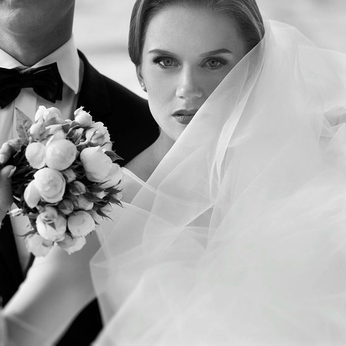 Vestuvių fotografas fotografuoja nuotaką prie jūros