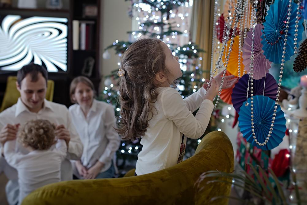 mergaitė tyrinėja kalėdinius žaisliukus