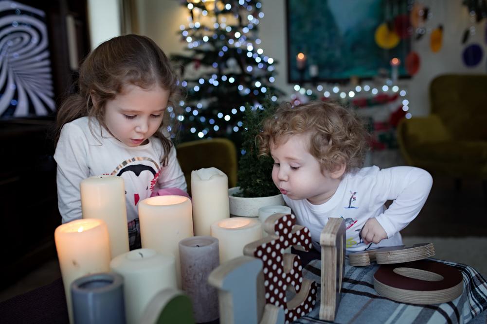 vaikai pučia kalėdines žvakes prie eglutės