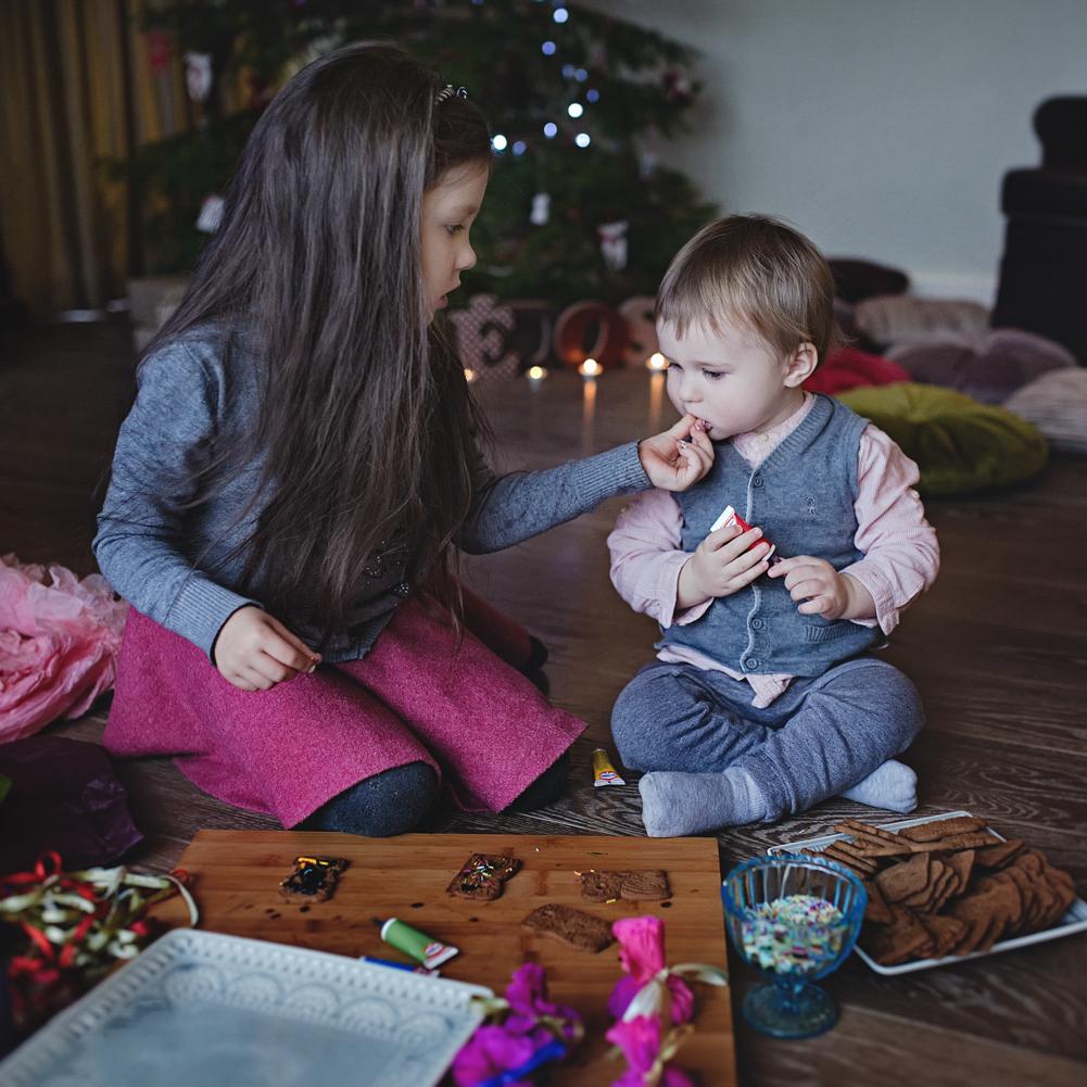 mergaitė kūdikiui duoda paragauti Kalėdinį meduolį