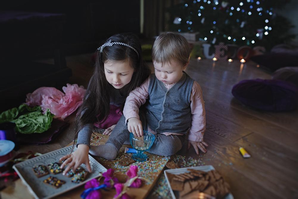 mergaitė ir kūdikis lipdo kalėdinius meduolius