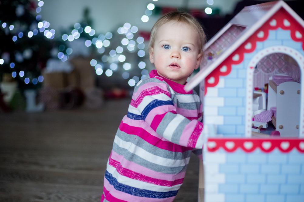mergaitė žaidžia, tolumoje matyti šviečianti Kalėdinė led girlianda
