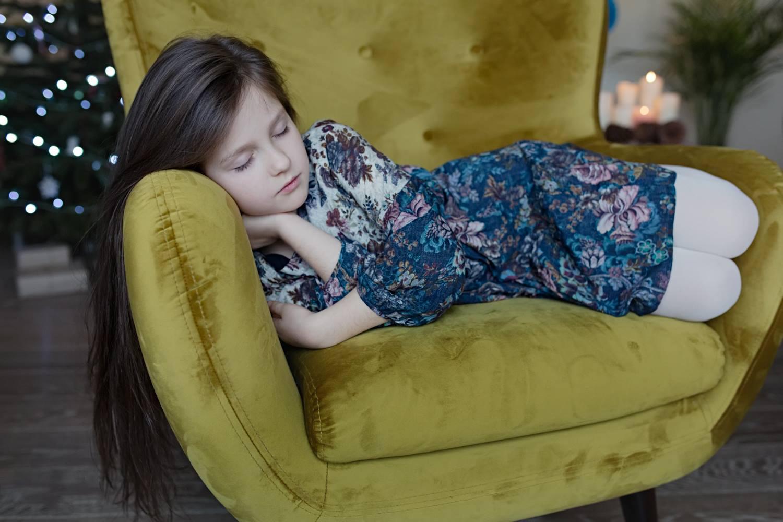 Mergaitė miega prie Kalėdinės eglutės