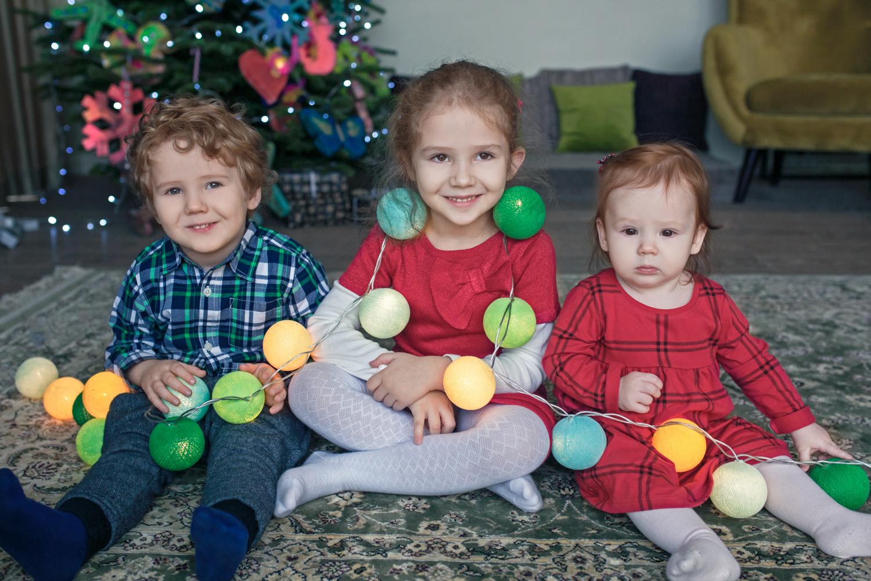 vaikai pasipuoše Kalėdine uogų girlianda studijoje