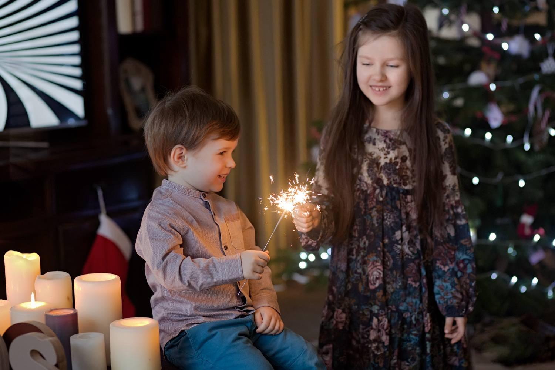 vaikai žaidžiai su liepsnos ugnelėmis prie Kalėdinės eglutės
