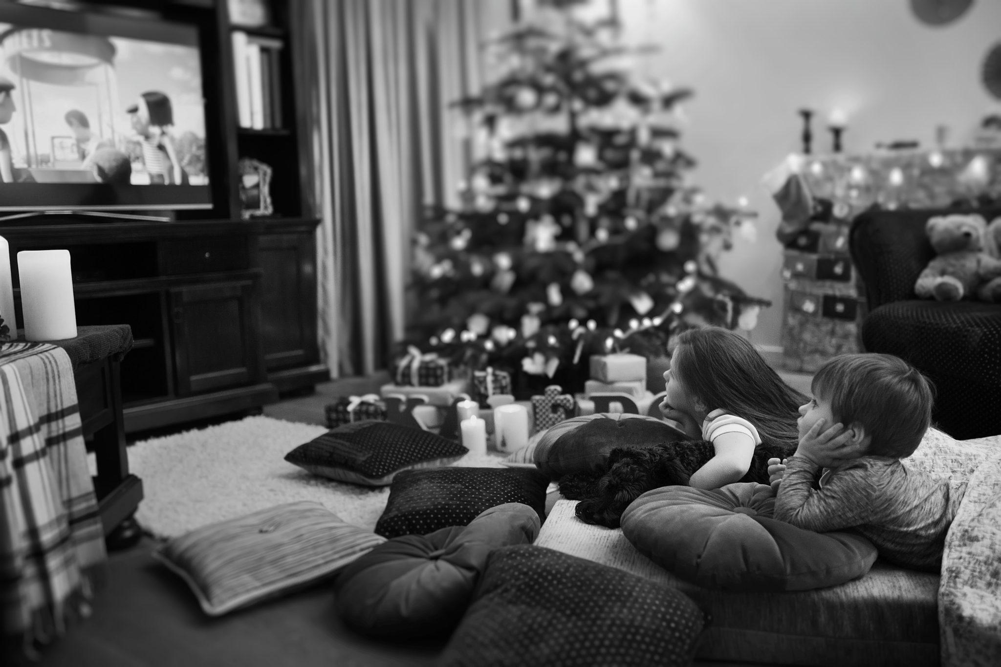 Kalėdinė šeimos fotosesija idėja - vaikai žiūri filmukus