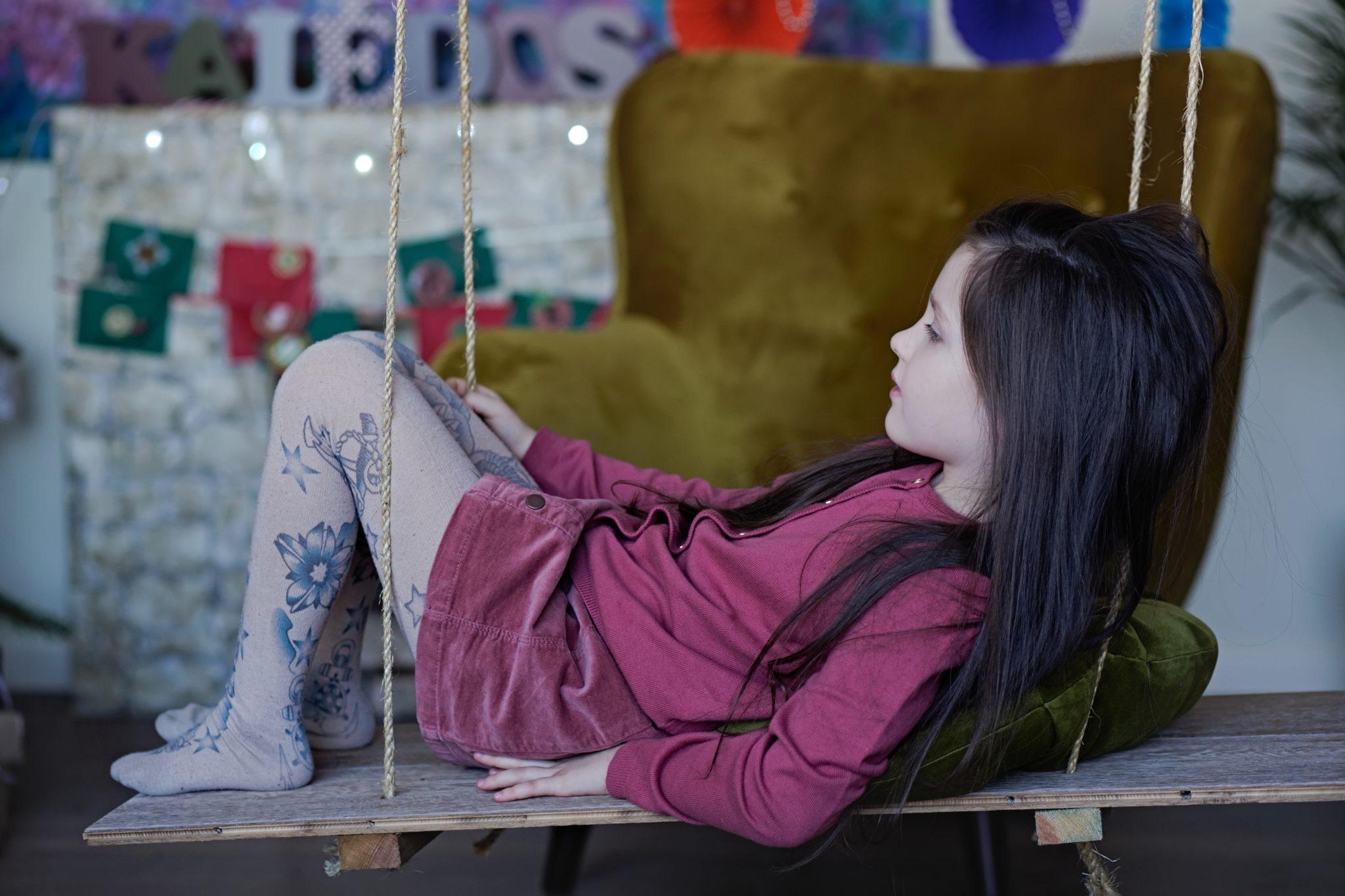 mergaitė supasi ant supyniu per Kalėdinę fotosesiją studijoje