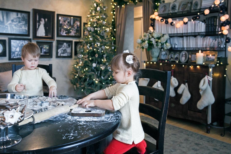 Mergaitė kočioja Kalėdinį sausainį tolumoje matosi Kalėdų eglė