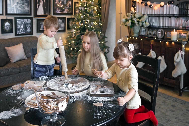 Berniukas su kočėlu daužo per stalą namuose. Namui papuošti Kalėdine atributika