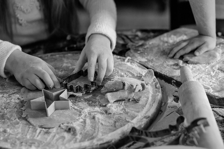 Mergaitė su sausainių formele pjauna Kalėdinę sraigę