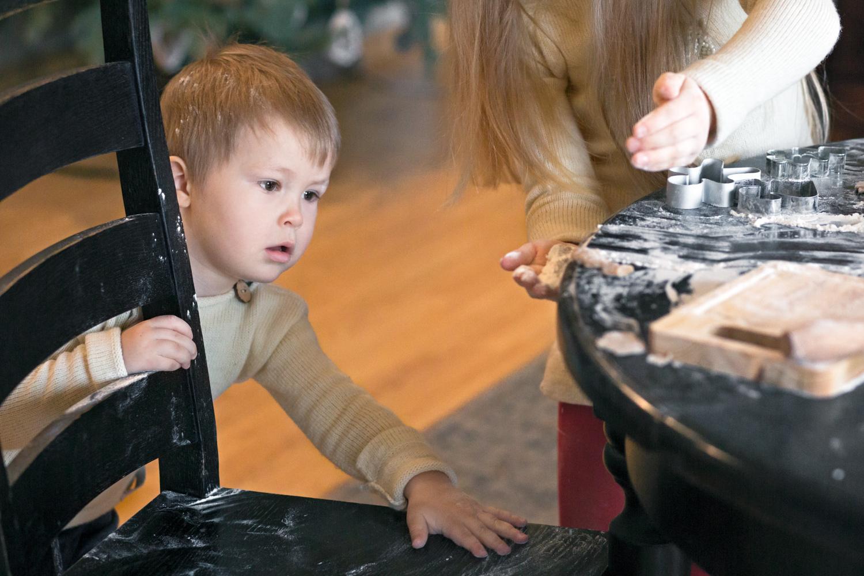 Bernkiukas po stalu renka Kalėdinių sausainių miltus