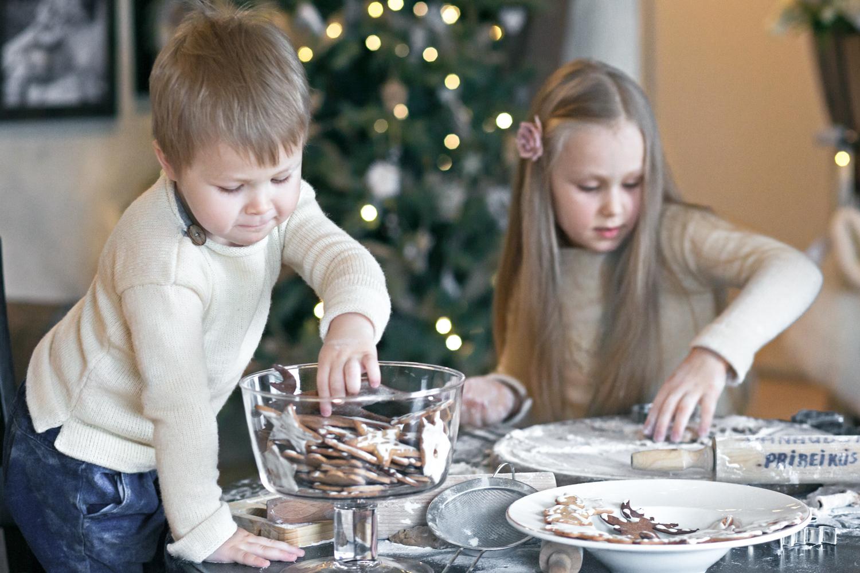 Berniukas valgo sausainį per Kalėdinę šeimos fotosesiją