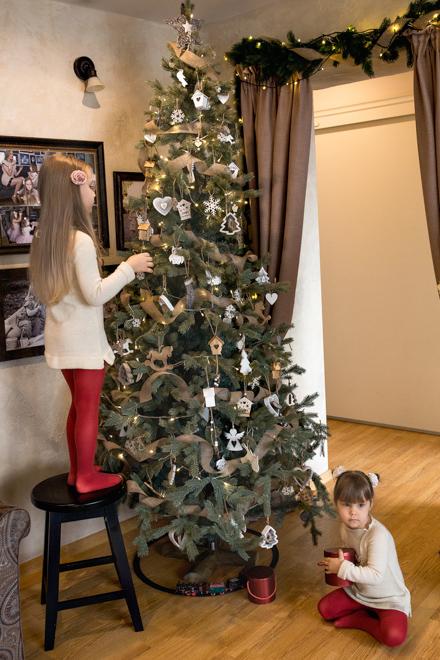 Mergaitės puošia Kalėdų eglę
