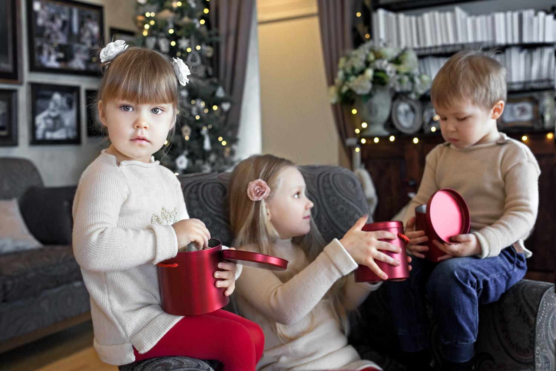 Vaikai valgo saldainius per kalėdinę šeimos fotosesiją