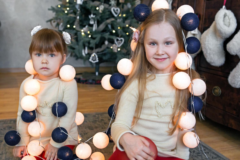 Mergaitės pasipuošusios Kalėdinėmis uogų girliandomis