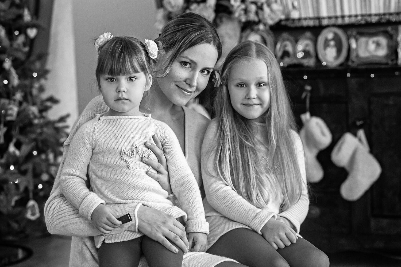 Mama su mergaitėmis fotografuojasi namuose