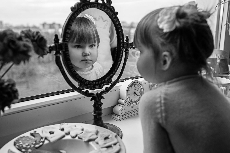 Mergaitė žiūri į veidrodį, šalia padėti Kalėdiniai sausainiai