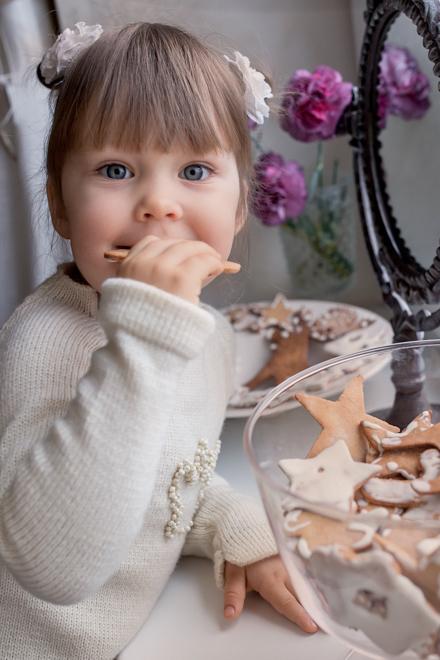 Mergaitė valgo Kalėdinį meduolį