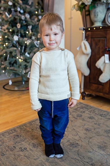 berniukas stovi prie Kalėdinės eglės