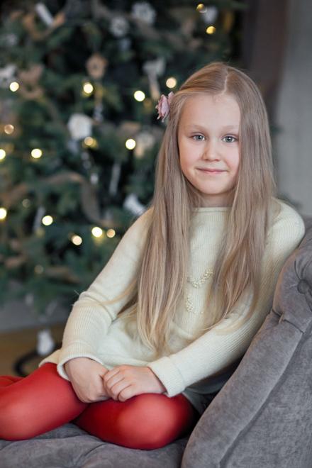 Mergaitė sėdi prie kalėdinės eglės