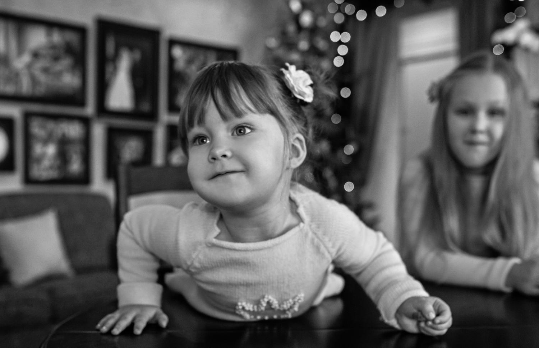 Mergaitė guli ant stalo per Kalėdinę šeimos fotosesiją
