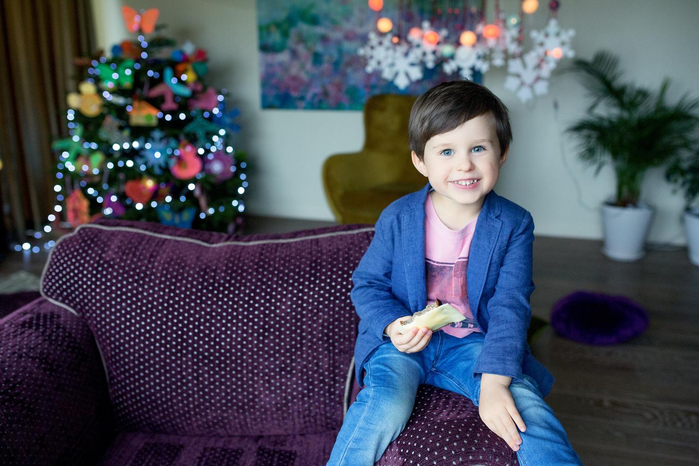 berniukas valgo sumuštinį per Kalėdinę fotosesiją studijoje