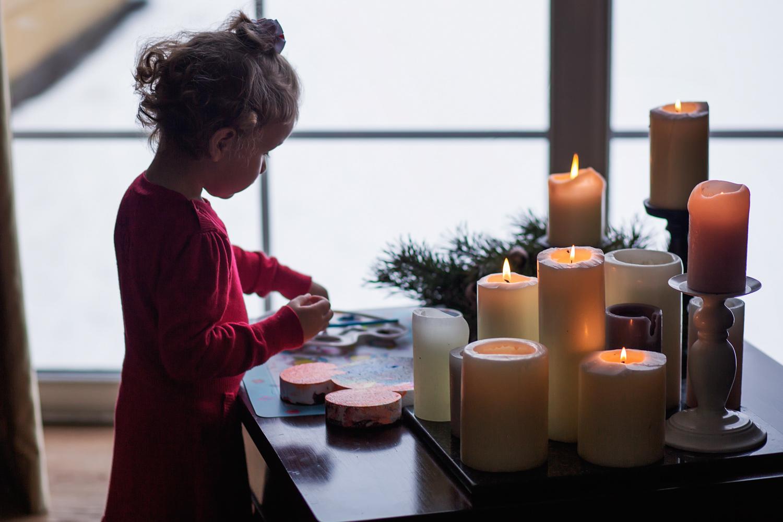 Mergaitė spalvina žvakių šviesoje per Kalėdinę šeimos fotosesiją studijoje