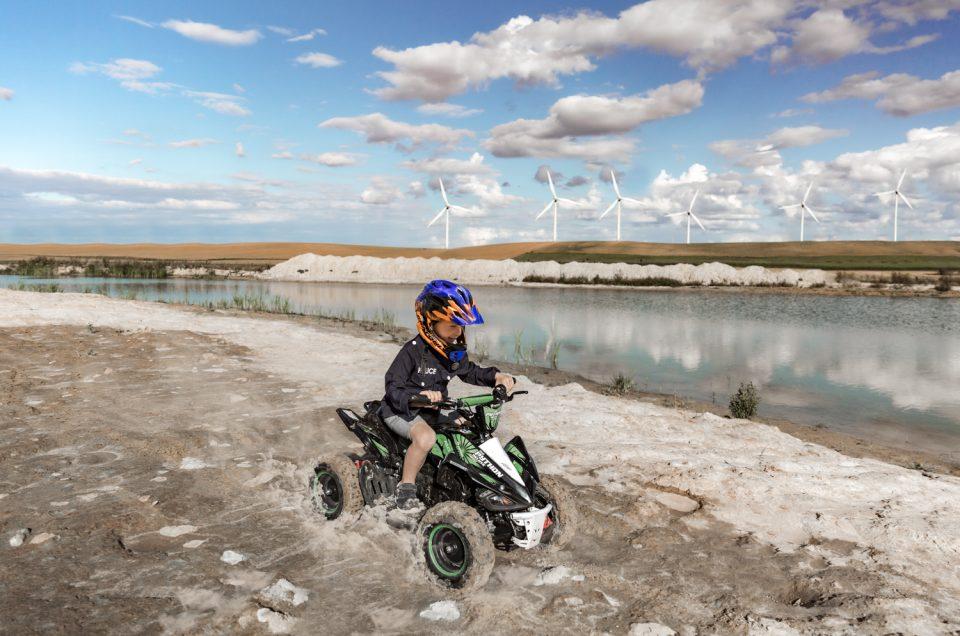 Vaikas su Cratoni šalmu važiuoja Python keturračiu smėlio karjere