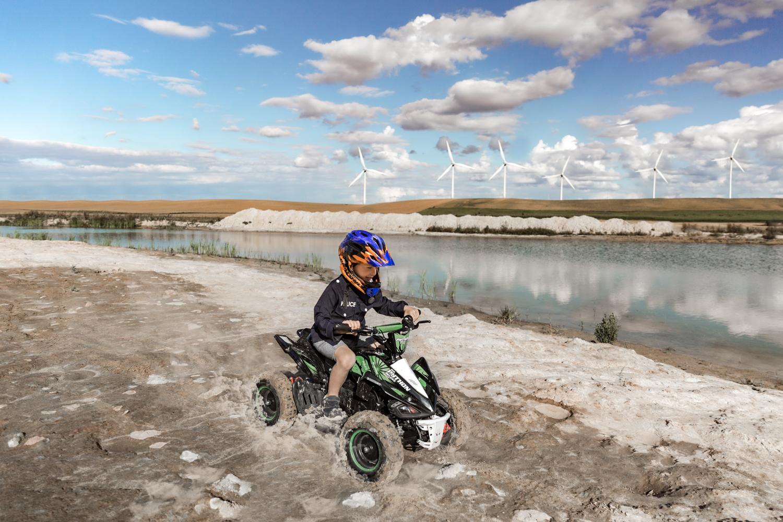 berniukas su šalmu važiuoja keturračiu smėlio karjere, tolumoje matosi vėjo turbinos