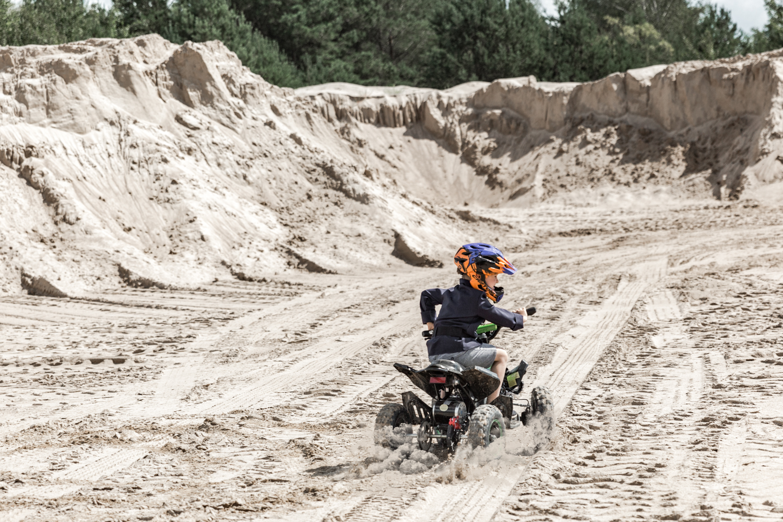 Žmogus su Cratoni šalmu važiuoja per smėlį ant keturračio