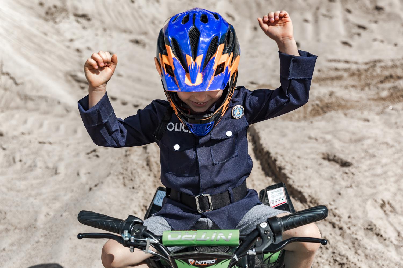 Vaikas su mėlynos spalvos Cratoni šalmu ant žalio keturračio iškėlęs rankas džiaugiasi