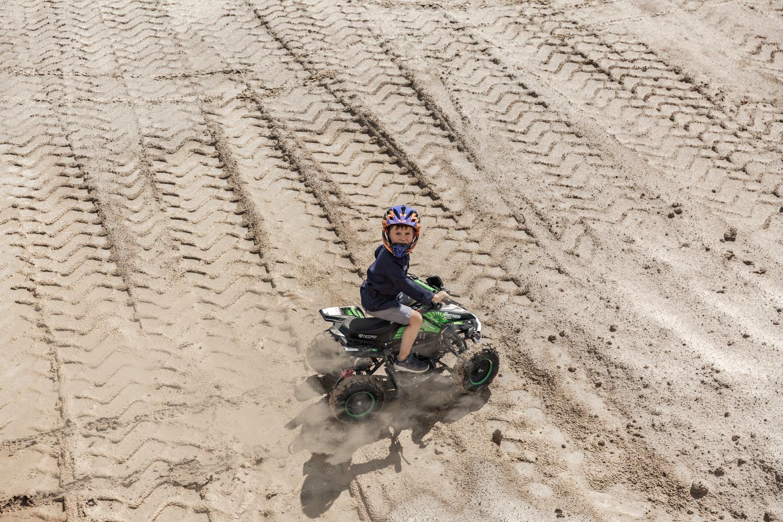 Vaikas su šalmu smėlio karjere važiuoja ant žalio keturračio, matosi ratų žymės