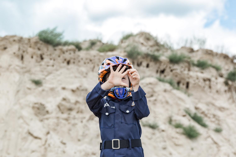 Policininko kostiumą apsivilkęs berniukas su šalmu, delnu rodo metų skaičių